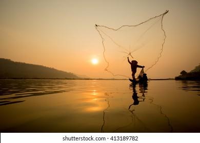 fisherman throwing fishing net during sunset