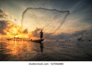 Fisherman throwing fishing net during sunrise in Pak Pra, Phatthalung, Thailand