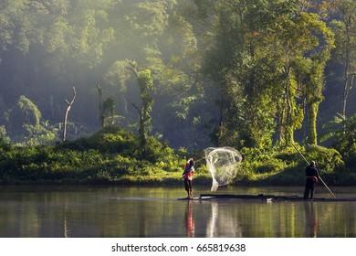 Fisherman Throwing His Net in a Beautiful Lake of Situ Gunung, West Java Indonesia. 24 August 2013