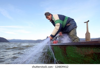 Fisherman throwing net from the boat