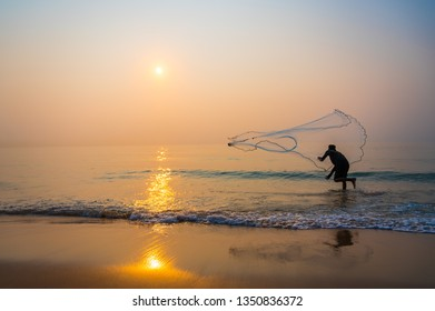 Fisherman throwing a net to the sea in morning time