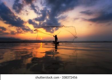Fisherman throwing net at sunrise , Thailand