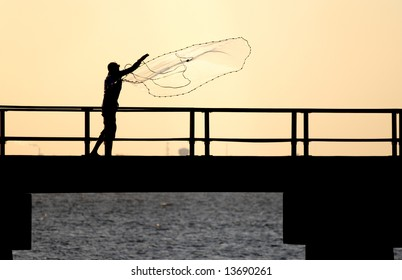Fisherman tossing a net from a pier.