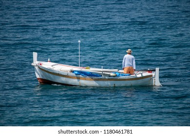 Fisherman in traditional wooden boat at sea, facing awaz from viewer, going out to sea, daylight, authentic and unstaged, mediterranean style, could be Italy, Greece, Croatia or Adriatic sea