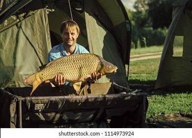 fisherman with a trophy. Carp fishing, angling, fish catching. Carp trophy, success, achievement in hands of happy fisherman man.