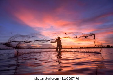 The fisherman trowing the nets on during sunset,Thailand