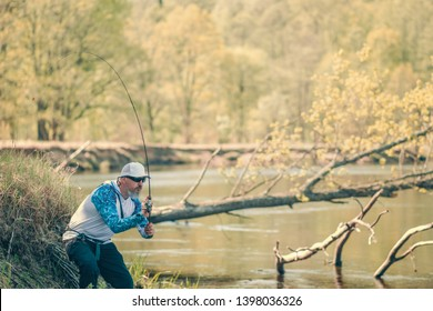 Fisherman trying to do a perfect cast, throwing lure. Spining fishing, angling, catching fish. Hobby and vacation.