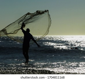 A fisherman trying to fish in the day and sunset