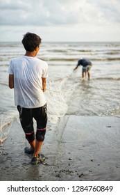 fisherman using trawl catching fish at beach