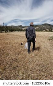 Fisherman walking with fly rod and fishing net through grass next to a river