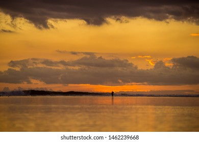 Fisherman walking on the ocean against the background of waves and incredible sunset. Mauritius, Indian Ocean