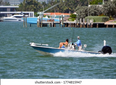 Fisherman and wife speeding on the Florida Intra-Coastal Waterway off Miami Beach in an open blue and white fishing skiff.