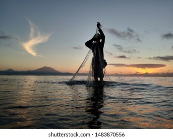 Fisherman at  work. Early morning view in the beach with fisherman silhouette, Mount Agung volcano and the sunrise background. Sanur Beach, Bali, Indonesia