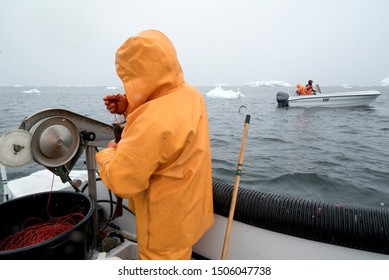 Fisherman working in a boat in arctic ocean, greenland. may 19, 2016
