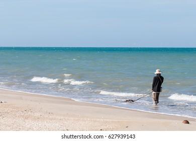 Fisherman working at sea beach on daytime