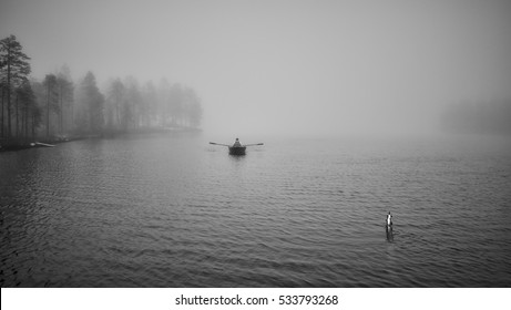 Fisherman's boat on eerie misty lake in black and white. Moody nature background.