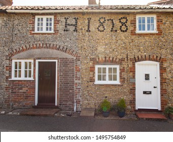 Fishermans cottage built of flint and stone with the year it was built embedded in the wall using bottle bottoms.