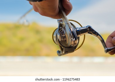 Fisherman's hand with fishing rod and reel