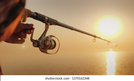 The fisherman's hands, holds the spinning rod, rotates the coil handle. Hobby and activity