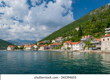 Fisherman's village Lepetane landscape with old houses, fishing boats and the Mountains of The Bay of Kotor. Montenegro
