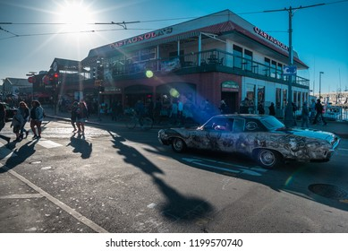 Fishermans Wharf, San Francisco, California, USA - May 27, 2018: Old vintage American car giving way to tourists at traffic lights on intersection at Castagnola's seafood restaurant at Pier 45