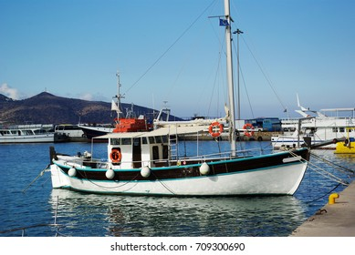 Fisherman's white boat moored in the harbor. Greece, Crete.