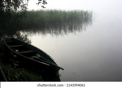 Fisherman's wooden boat in the mist, lake Balotes near Jekabpils, Latvia