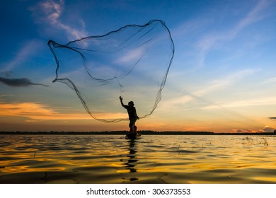 Fishermen in action when fishing in the lake , Thailand