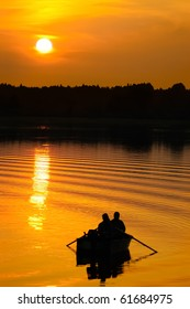 Fishermen in boat at colorful orange sunset, silhouettes against the setting sun