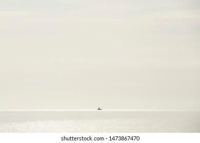 Fishermen boat silhouette against orange sunrise on Lake Malawi, the sun glitter on the Lake, South-East-Africa