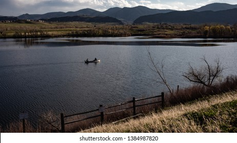 Fishermen boating on Bear Creek Lake with rocky mountains and clouds in background