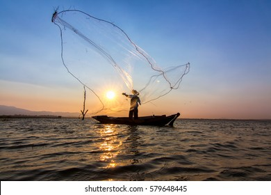 Fishermen cast net into the water in the morning. The silhouette of a fisherman in lifestyle.
