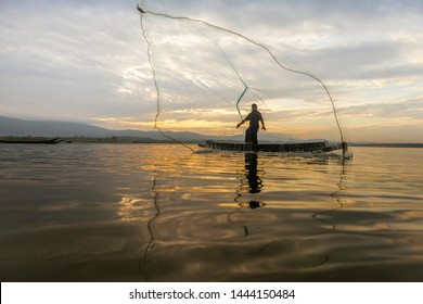 Fishermen Casting are going out to fish early in the morning with wooden boats, old lanterns and nets. Concept Fisherman's life style.