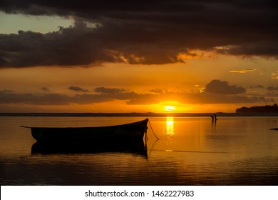 Fishermen catch fish on the background of boats and colorful sunset. Mauritius, Indian Ocean
