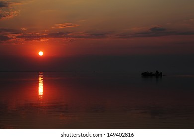 Fishermen catch fish on a background of a sunset