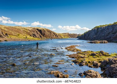 Fishermen catch fish in the river near the waterfall Laxfoss