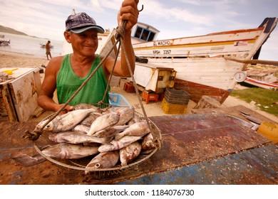 fishermen at the fish market on the beach in the town of Juangriego on the Isla Margarita in the caribbean sea of Venezuela.   Venezuela, Caracas, November, 2005