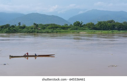 Fishermen fish in the Mekong River There is a high mountain backdrop.
