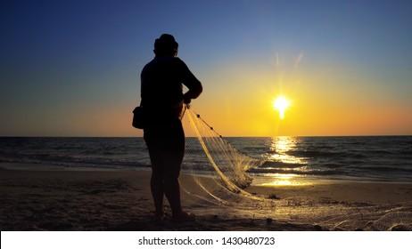 Fishermen fishing in the early morning golden light manual hand pulling the net