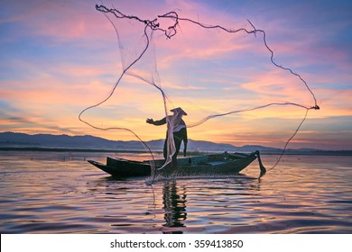 Fishermen fishing in the early morning golden light.Fishermen on a fishing boat.Fishermen are casting nets.Sparkling water.