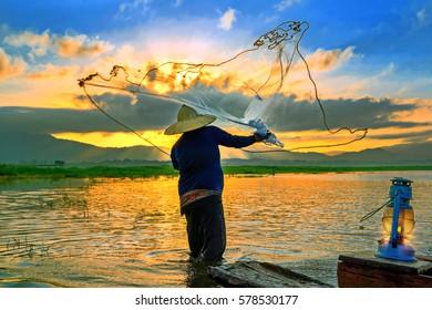 Fishermen fishing in the early morning golden light.