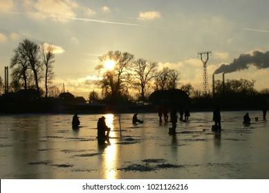 fishermen fishing on a frozen lake