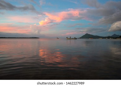 Fishermen go on a boat for evening fishing on the background of a colorful sunset. Mauritius, Indian Ocean
