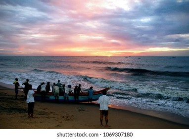 Fishermen going on a boat in the ocean for fishing during morning sunrise at Auroville Beach, Pondicherry (Puducherry), Tamil-Nadu, India