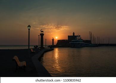 Fishermen and lighthouse in Mandraki harbor in City of Rhodes (Rhodes, Greece)