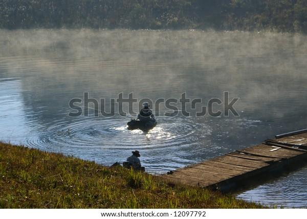 Fishermen in morning mist