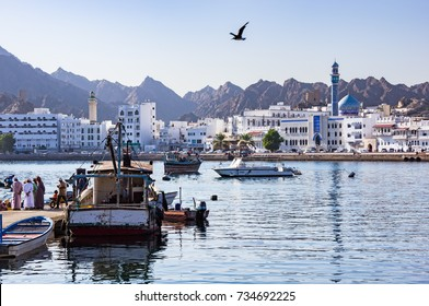 Fishermen at The Muttrah Fish docks with Muttrah corniche in the Background - Muscat, Oman