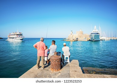 Fishermen near entrance into Mandraki harbor in City of Rhodes (Rhodes, Greece)