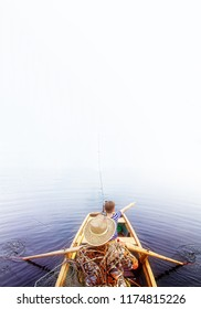 fishermen on a boat in the fog. old and young fisherman on a boat among the water and fog. Vertical. Copy space for your text