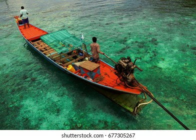 Fishermen on a boat in a turquoise sea water